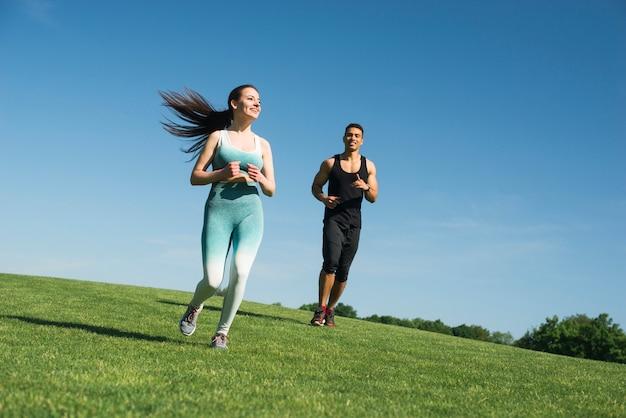 Homme et femme qui court en plein air dans un parc