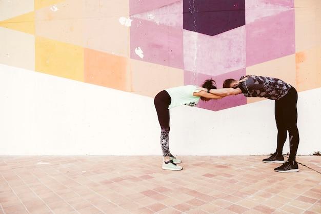 Homme et femme qui s'étend devant le mur de graffitis