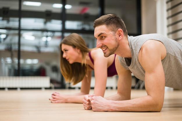 Homme et femme qui s'étend à la gym