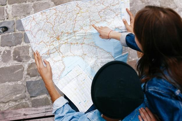 Homme et femme regardent la carte assis sur le banc quelque part dans une vieille ville
