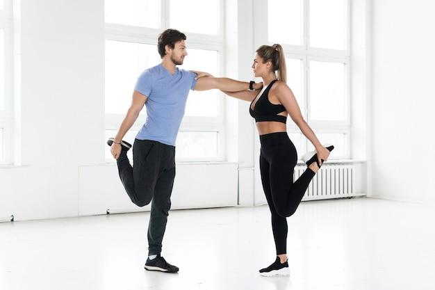 Homme et femme de remise en forme pendant l'entraînement avec dans la salle de gym. échauffement des muscles quadriceps.