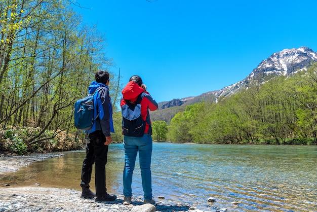 Homme et femme avec la rivière azusa et le mont yake à kamikochi, dans les alpes du nord du japon.