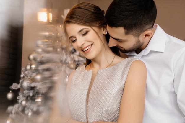 Un homme et une femme en robe argentée s'embrassent devant un arbre de noël