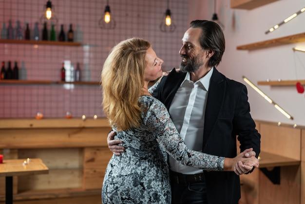 Homme et femme s'amusant dansant dans un restaurant se regardant dans les yeux