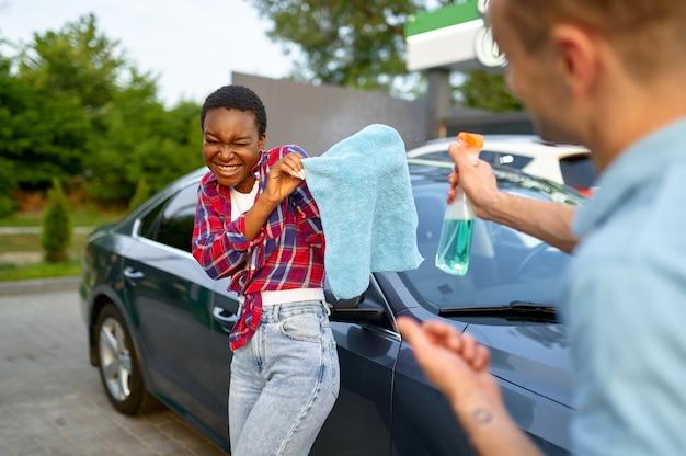 Homme et femme s'amusant sur la station de lavage de voiture à la main. industrie ou entreprise de lavage de voitures. homme et femme plaisantant sur le service de lavage de voiture à l'extérieur