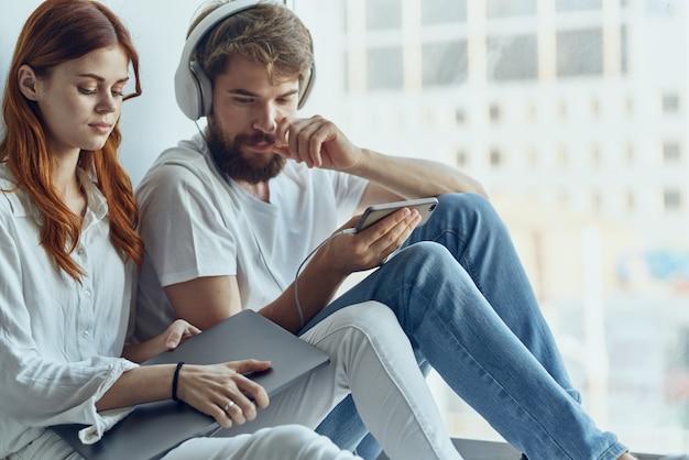L'homme et la femme s'assoient près de la fenêtre avec des écouteurs aiment la technologie de style de vie