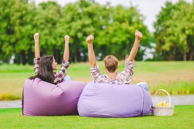 L'homme et la femme s'assoient sur le sac de haricots et font un geste