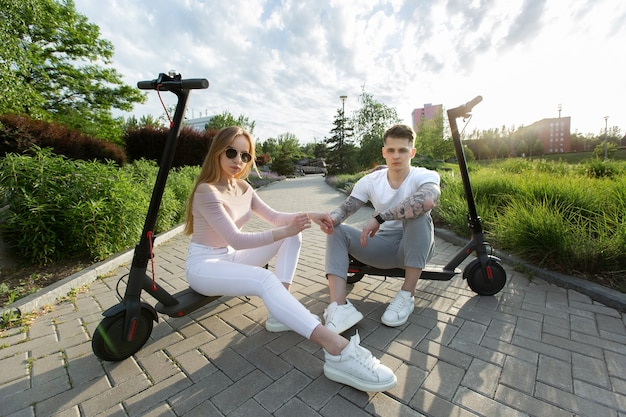 Un homme et une femme s'assoient sur des scooters électriques dans le parc