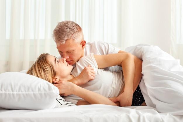 Homme et femme s'embrassant au lit