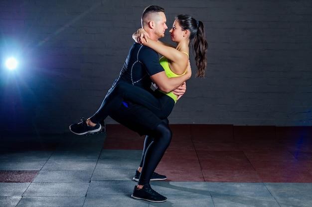 L'homme et la femme s'entraînent ensemble dans la salle de sport sur fond de briques noires. des sit-ups coopératifs