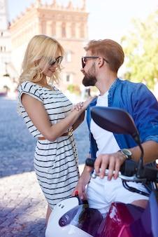 Homme et femme avec scooter dans la rue de la ville