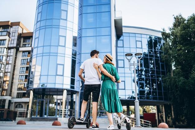 Homme et femme sur des scooters électriques noir et blanc.