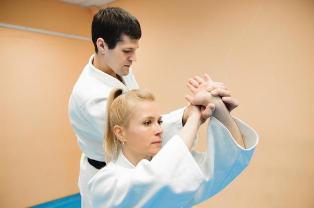 Homme et femme se battant à la formation d'aïkido à l'école d'arts martiaux