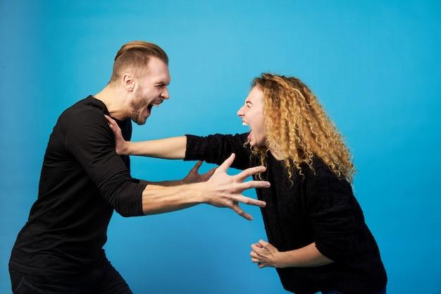 Homme et femme se criant dessus, se querellant et se battant.
