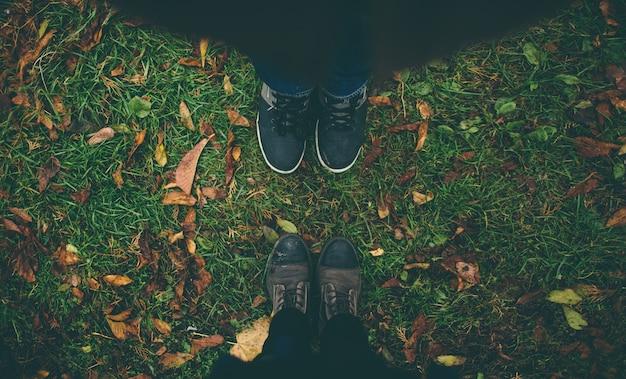 L'homme et la femme se font face. gros plan des pieds en bottes d'hiver dans la pelouse d'automne