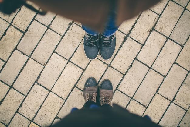 L'homme et la femme se font face. gros plan des pieds en bottes d'hiver dans la rue