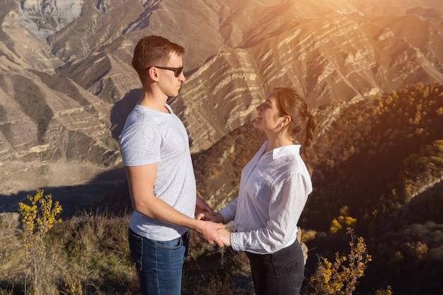 Un homme et une femme se font face, se tenant la main sur le fond des montagnes, la lumière du soleil.