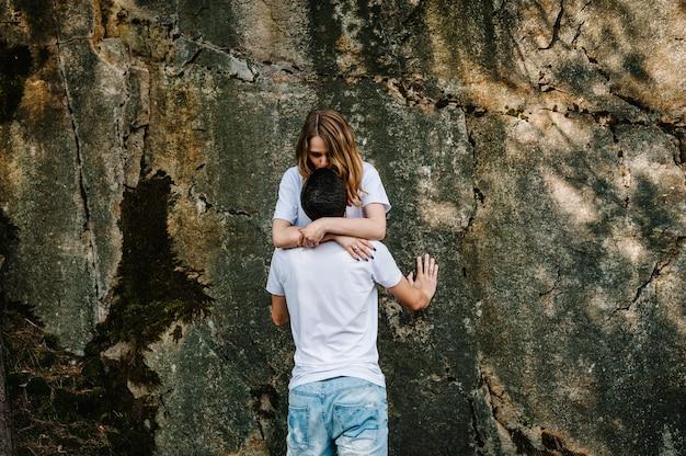 Un homme et une femme se lèvent et s'embrassent, s'embrassent près d'un gros rocher