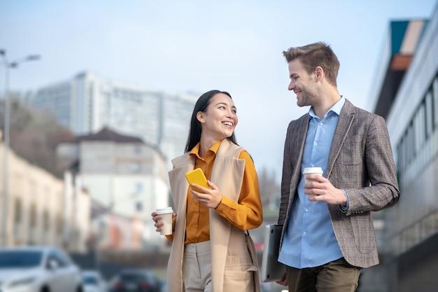 Homme et femme se regardant joyeusement en traversant la rue