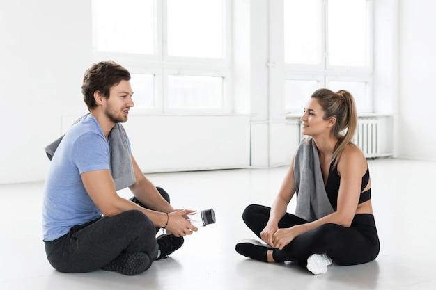 Homme et femme se reposant après l'entraînement de remise en forme callisthénique dans la salle de sport