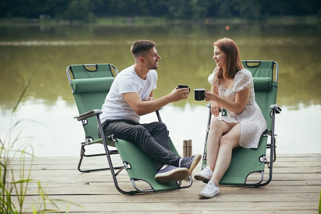 Homme et femme se reposant ensemble sur des chaises au bord du lac et buvant du café