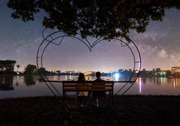 Homme et femme se reposant sur le rivage sous le ciel nocturne