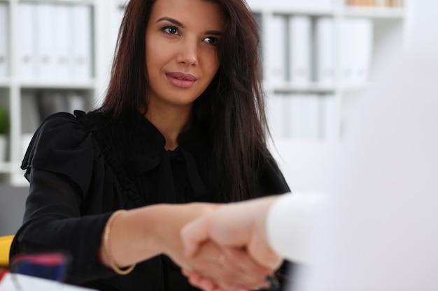 Homme et femme se serrent la main comme bonjour au bureau