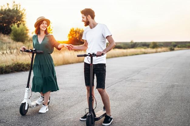 Homme et femme se tenant la main. sur la route de fond et le coucher du soleil. marcher sur des scooters électriques