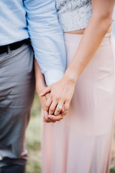 L'homme et la femme se tiennent côte à côte, la femme tient l'homme par la main en gros plan