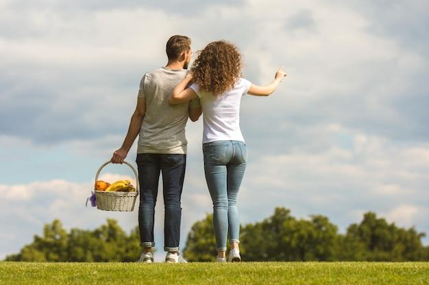 L'homme et la femme se tiennent sur l'herbe et tiennent un panier avec des fruits