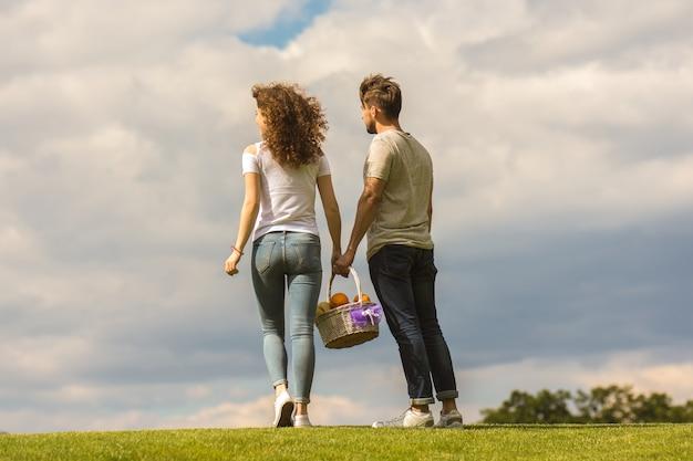 L'homme et la femme se tiennent sur l'herbe et tiennent un panier