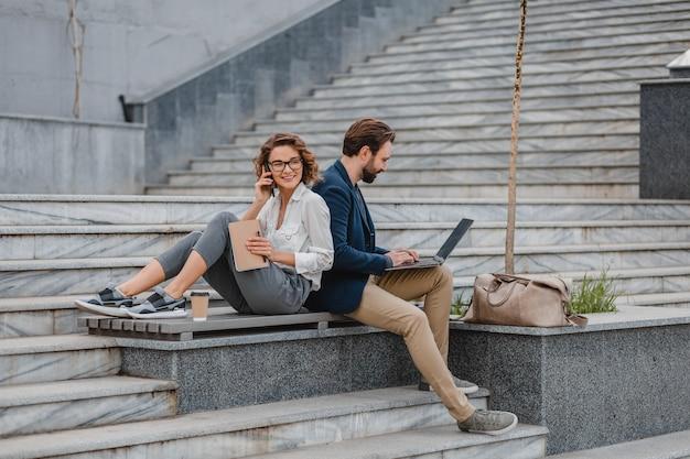 Homme et femme séduisants assis dans les escaliers du centre-ville urbain, travaillant ensemble sur un ordinateur portable