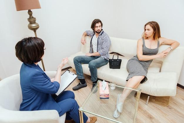 Un homme et une femme séduisants sont assis et se regardent. ils ont l'air triste. ces gens travaillent avec un psychologue. le thérapeute tend la main et pointe du doigt.