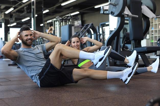 Homme et femme séduisants travaillant par paires effectuant des redressements assis dans une salle de sport.