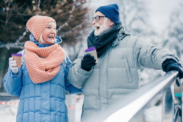 Homme et femme senior positifs avec des tasses de café marchant en hiver et se regardant avec un sourire heureux