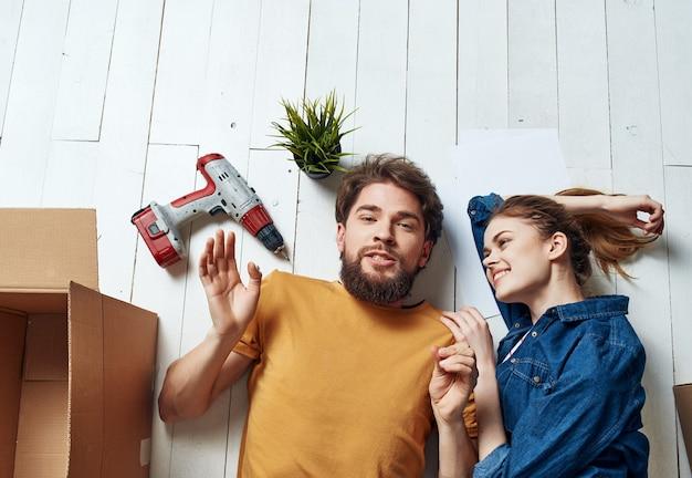 L'homme et la femme sont allongés sur le sol dans une pièce avec des boîtes en mouvement