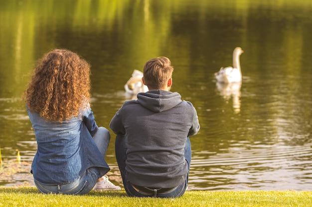 L'homme et la femme sont assis au bord de la rivière
