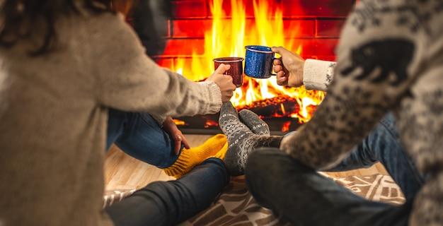 L'homme et la femme sont assis à côté de la cheminée, qui est représentée sur l'écran du téléviseur et boivent une boisson chaude