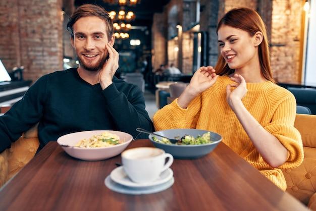 Un homme et une femme sont assis à une table dans un repas au restaurant de délicieux plats servant des plats