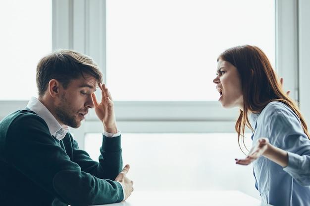 Un homme et une femme sont assis à une table en train de se disputer, une vraie querelle, des problèmes de ménage