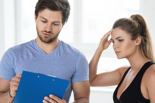L'homme et la femme sont prêts à s'entraîner dans la salle de sport. instructeur de conditionnement physique personnel écrivant un plan d'entraînement et de régime individuel pour son client