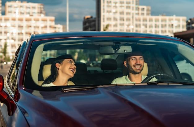 L'homme et la femme souriants assis dans la voiture