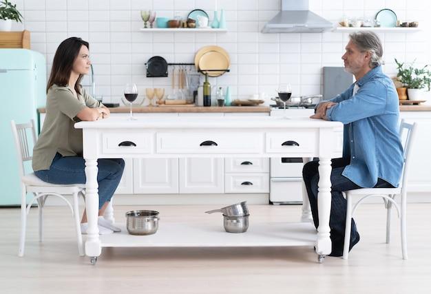 Homme et femme souriants discutant, buvant du vin rouge dans une cuisine moderne, femme et mari heureux tenant des lunettes, assis à table, célébrant un anniversaire, un rendez-vous romantique ou passant le week-end à la maison