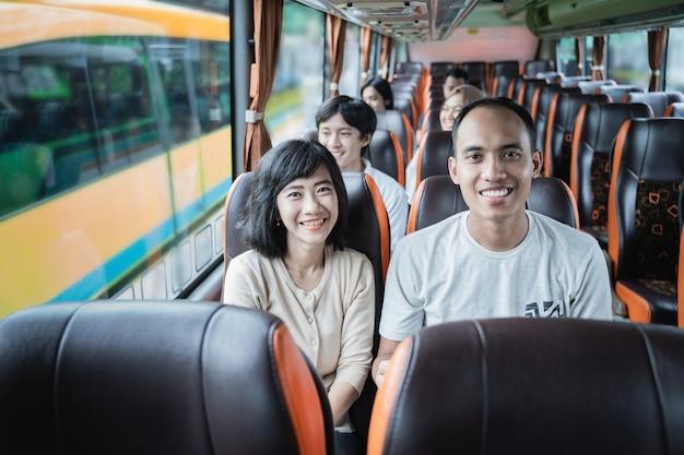 Un homme et une femme sourient assis dans le bus lors d'un voyage