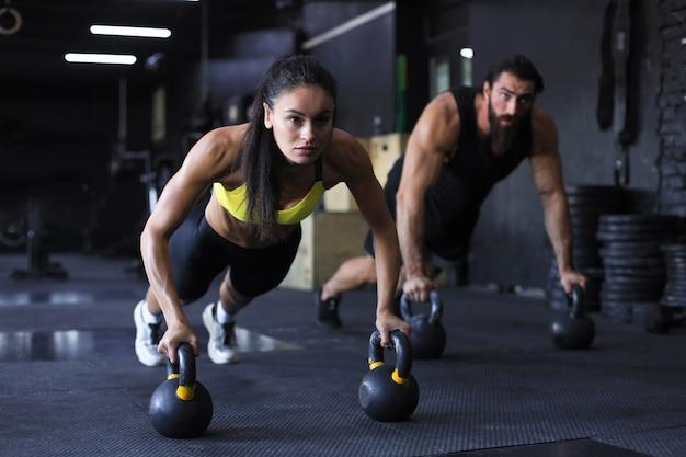 Homme et femme sportifs faisant des pompes dans une salle de sport.