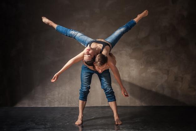 L'homme et la femme de style moderne dans la pose de danse passionnée sur le dos gris