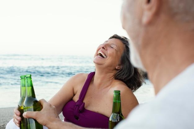 Homme et femme supérieurs riant sur la plage tout en buvant de la bière
