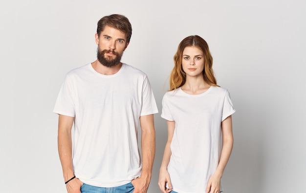 Homme et femme en t-shirts blancs émotions amusantes maquette de studio