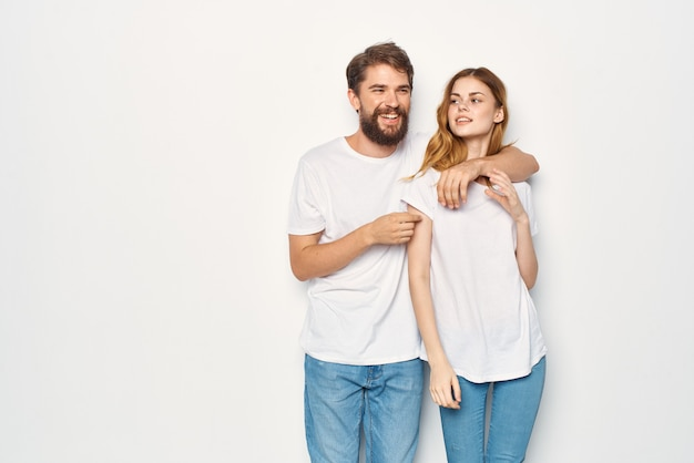 L'homme et la femme en t-shirts blancs se tiennent à côté du fond clair de la famille. photo de haute qualité
