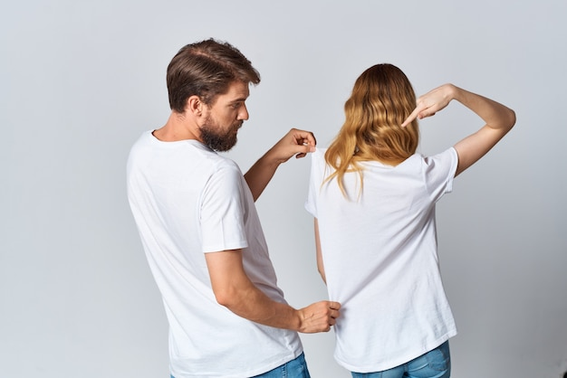 L'homme et la femme en t-shirts blancs se tiennent avec leur maquette de fond clair de dos